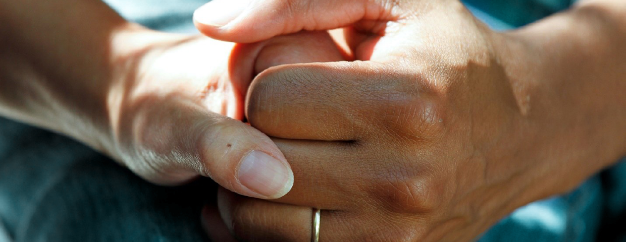 A person holding their friend's hand in support.